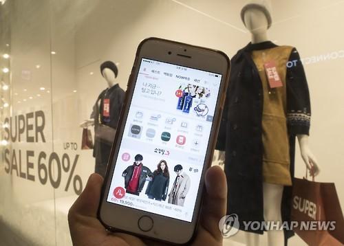 モバイル端末を利用して買い物をする市民(資料写真)=(聯合ニュース)