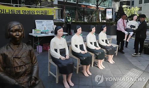 日本大使館前に設置された少女像の横に置かれるレプリカ=2日、ソウル(聯合ニュース)