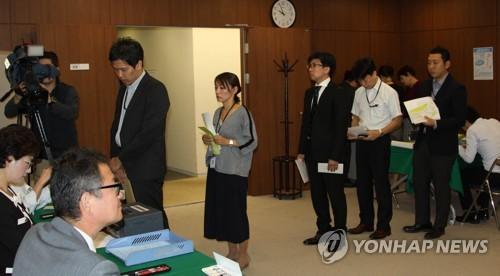 ソウルの日本大使館に設置された投票所で投票を行う有権者たち=11日、ソウル(聯合ニュース)