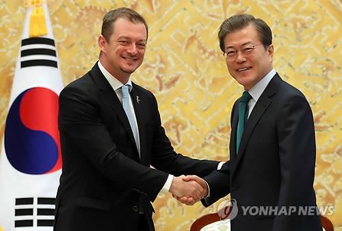 IPCのパーソンズ会長(左)と握手する文大統領=17日、ソウル(聯合ニュース)