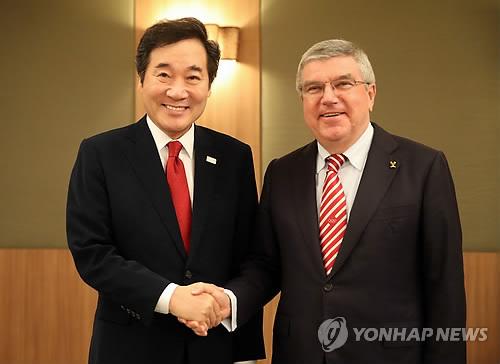 握手を交わす李首相(左)とバッハ会長=24日、オリンピア(聯合ニュース)