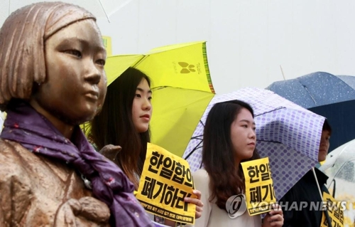慰安婦被害者を象徴する少女像のそばで韓日合意の破棄や「和解・癒やし財団」の解散を求める人々(資料写真)=(聯合ニュース)