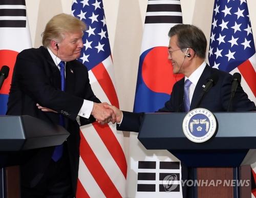 共同記者会見で握手を交わす文大統領(右)とトランプ大統領=7日、ソウル(聯合ニュース)