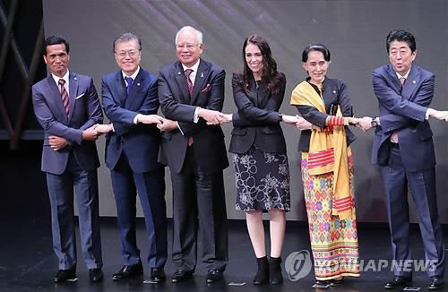 ASEAN首脳会議の開会式で各国首脳と手をつなぐ文大統領(左から2人目)=13日、マニラ(聯合ニュース)