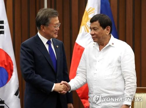 フィリピンのドゥテルテ大統領(右)と握手する文大統領=13日、マニラ(聯合ニュース)