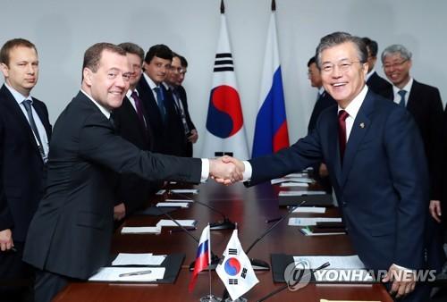 握手を交わす文大統領(右)とメドベージェフ首相=14日、マニラ(聯合ニュース)