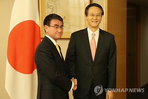 外務省で握手を交わす李氏(右)と河野氏=14日、東京(聯合ニュース)