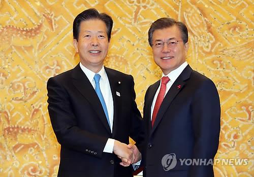 握手を交わす文大統領(右)と山口代表=23日、ソウル(聯合ニュース)