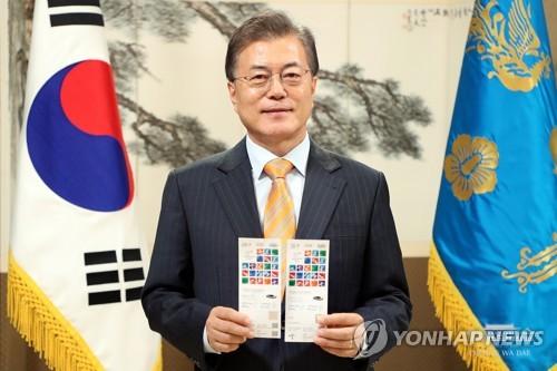 文大統領のツイッターに投稿された写真。入場券2枚を手にしている(ハロー平昌より)=26日、ソウル(聯合ニュース)