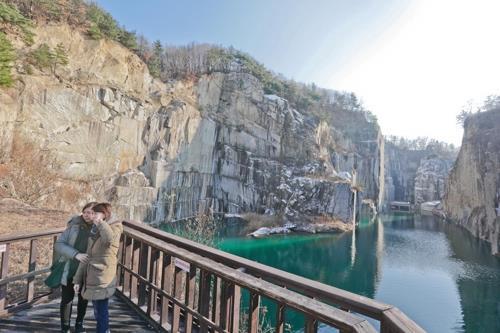 岩に囲まれた湖。台湾人観光客が写真を撮っている=(聯合ニュース)