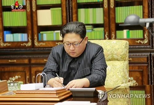 朝鮮中央テレビは火星15の発射命令を作成する金正恩(キム・ジョンウン)朝鮮労働党委員長の姿を公開した=29日、ソウル(朝鮮中央テレビ=聯合ニュース)