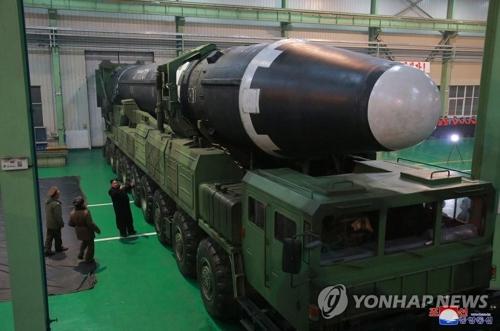 移動式発射台に積まれたミサイルと、傍らに立つ金正恩氏=(朝鮮中央通信=聯合ニュース)