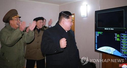 発射状況をモニターで見守る金正恩氏と関係者=(朝鮮中央通信=聯合ニュース)