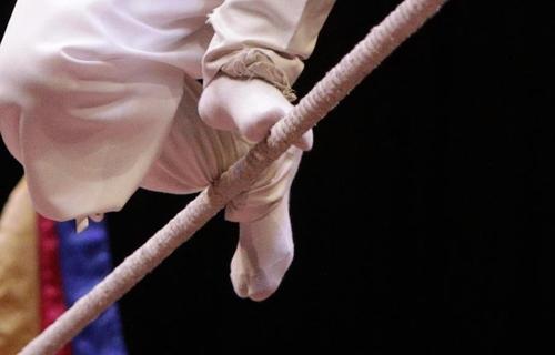 足の親指と足首で綱をつかんでバランスを取る=(聯合ニュース)