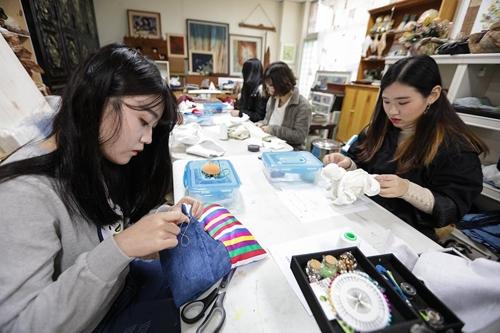 工芸文化センターで刺繍の実習を行う女子高生ら=(聯合ニュース)