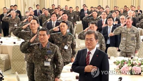 昼食会で国旗に敬礼する文大統領(手前右)と軍の指揮官ら=8日、ソウル(聯合ニュース)