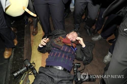 暴行を受けて倒れている韓国人記者=14日、北京(聯合ニュース)