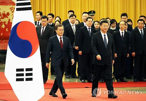 歓迎式の会場に入る文大統領(左)と習主席=14日、北京(聯合ニュース)