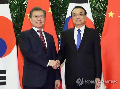 李克強首相(右)と握手する文大統領=15日、北京(聯合ニュース)