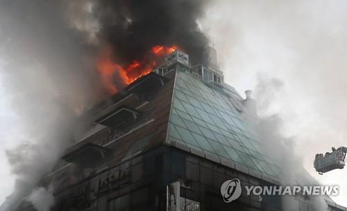 炎と煙が上がるビル=21日、堤川(聯合ニュース)