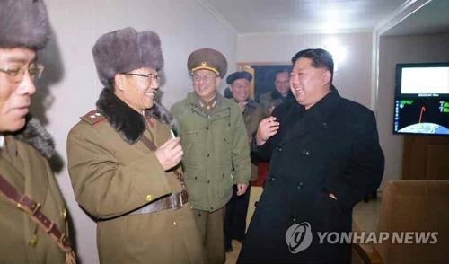 11月に弾道ミサイルの発射に立ち会った際、軍の幹部とたばこを吸いながら談笑する金委員長(右)=(聯合ニュース)