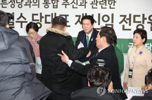 記者会見の途中で乱入した男が取り押さえられている=31日、ソウル(聯合ニュース)