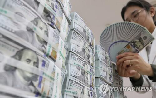 KEBハナ銀行本店でドル紙幣を確認する行員(資料写真)=(聯合ニュース)