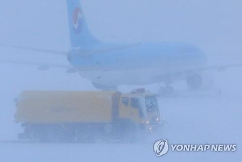 除雪作業が行われている済州国際空港=11日、済州(聯合ニュース)