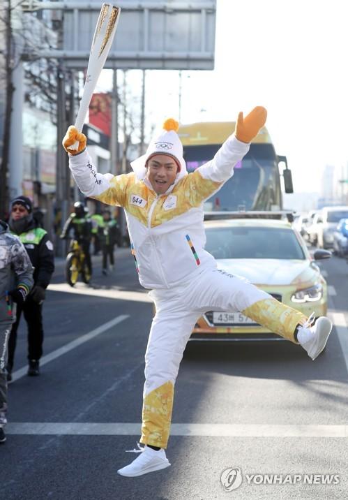 聖火リレー中、派手なジャンプのパフォーマンスを披露する高橋さん=12日、仁川(聯合ニュース)