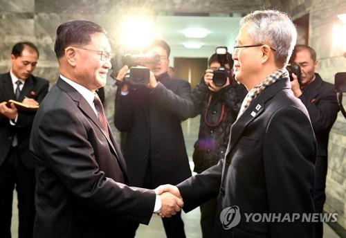 握手を交わす韓国首席代表の李宇盛氏(右)と北朝鮮代表の権ヒョク奉氏(統一部提供)=15日、板門店(聯合ニュース)