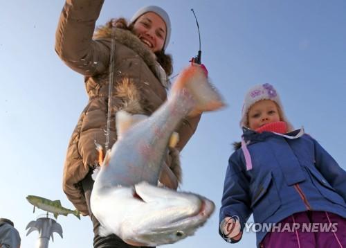 氷上釣りを楽しむ外国人観光客=14日、華川(聯合ニュース)