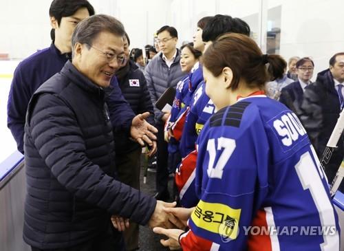 アイスホッケー女子代表の選手と握手を交わす文大統領=17日、鎮川(聯合ニュース)