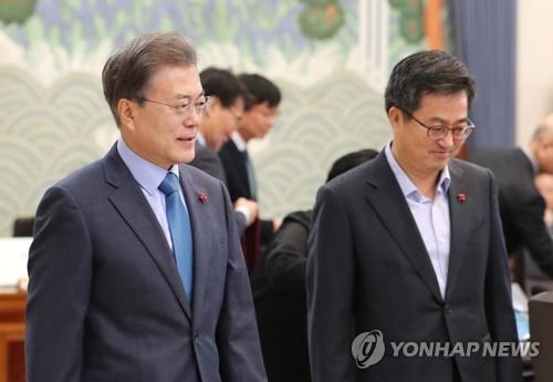 閣議に向かう文大統領(左)と金副首相=18日、ソウル(聯合ニュース)