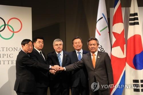 平昌冬季五輪への北朝鮮の参加を巡る韓国、北朝鮮、五輪組織委員会、国際オリンピック委員会(IOC)による4者協議で手を合わせる出席者=20日、ローザンヌ(聯合ニュース)