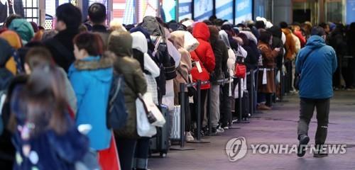 ソウル市内の免税店前に早朝から長い列を作る中国人客(資料写真)=(聯合ニュース)
