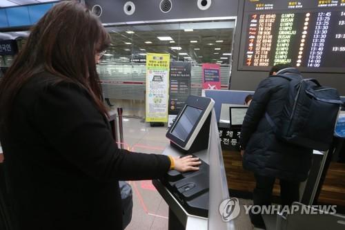 済州国際空港で手のひら認証システムを利用する搭乗客=29日、済州(聯合ニュース)