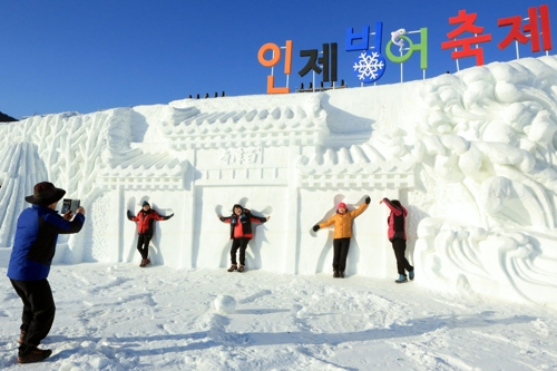 雪像の前で写真を撮る観光客ら=(聯合ニュース)
