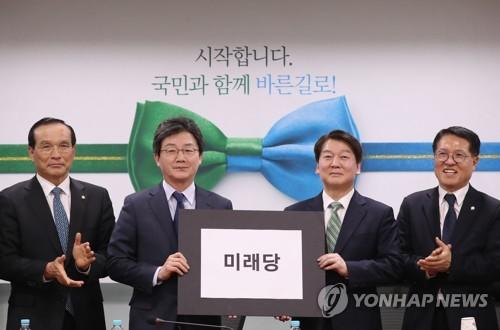 「未来党」と書かれたボードを持つ国民の党の安代表(右)と正しい政党の劉承ミン(ユ・スンミン)代表(正しい政党提供)=2日、ソウル(聯合ニュース)