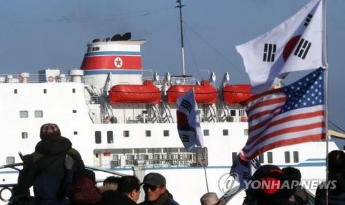 入港した万景峰92に向かい太極旗(韓国国旗)などを振って抗議する保守団体=6日、東海(聯合ニュース)