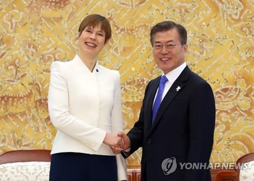 カリユライド大統領(左)と握手する文在寅大統領=6日、ソウル(聯合ニュース)