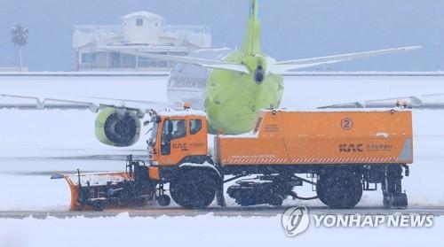 滑走路の除雪作業=8日、済州(聯合ニュース)