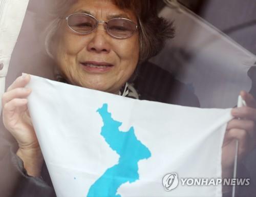 空港からバスに乗り、車内で朝鮮半島旗を手にしながら涙を浮かべる朝鮮総連の応援団=8日、ソウル(聯合ニュース)