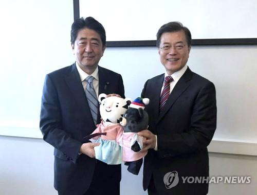2017年9月7日、ロシア・ウラジオストクで安倍首相(左)に平昌五輪・パラリンピックのマスコット人形を渡す文大統領=(聯合ニュース)