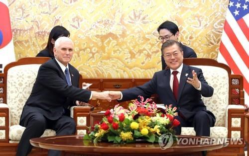 ペンス副大統領(左)と握手する文大統領=8日、ソウル(聯合ニュース)