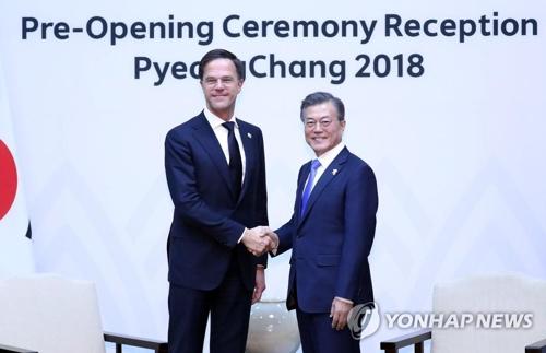握手を交わす文大統領(右)とルッテ首相=9日、平昌(聯合ニュース)