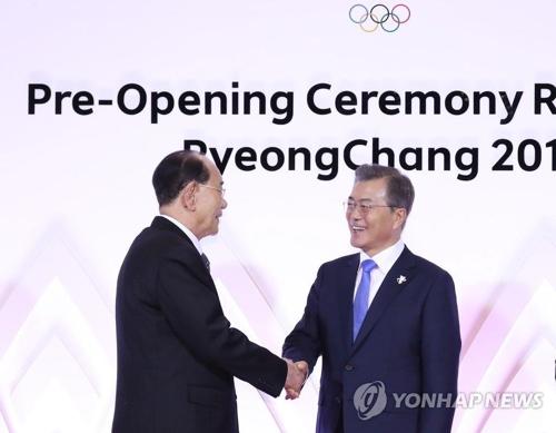 金永南氏(左)と握手する文大統領=9日、平昌(聯合ニュース)
