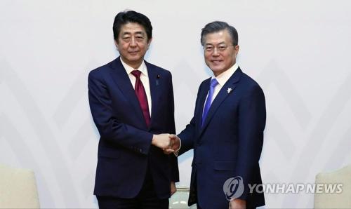 握手を交わす文大統領(右)と安倍首相=9日、平昌(聯合ニュース)