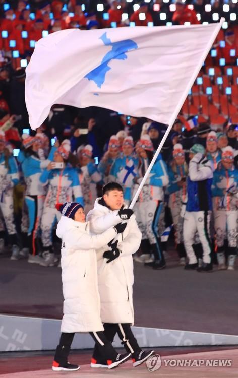 朝鮮半島旗を掲げて入場するウォン・ユンジョン(右)とファン・チュングム=9日、平昌(聯合ニュース)