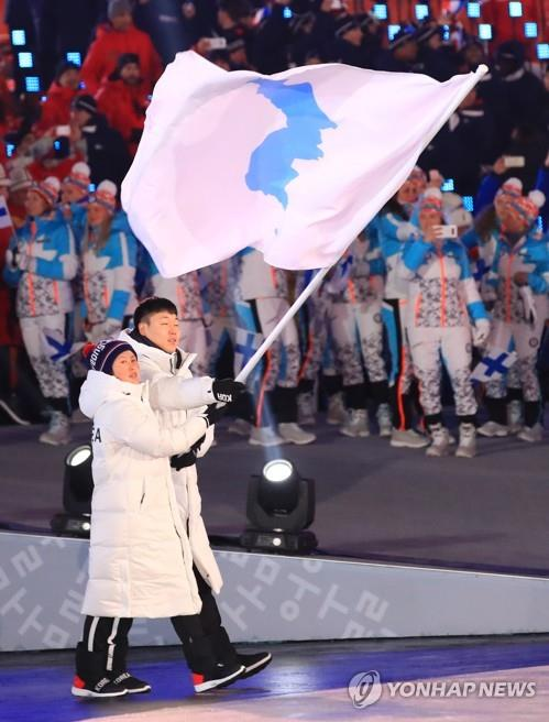 韓国のボブスレー男子のウォン・ユンジョンと北朝鮮アイスホッケー女子のファン・チュングムが朝鮮半島旗を掲げて入場行進を行った=9日、平昌(聯合ニュース)