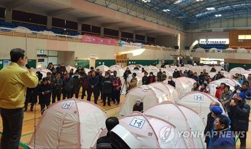 昨年11月の地震により室内体育館で避難生活をしている市民も今回の余震に不安を募らせた。マイクで状況を説明する浦項市長=11日、浦項(聯合ニュース)
